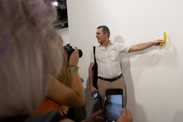 An Art Basel visitor places a banana in front of the wall where the artwork 'Comedian' by the artist Maurizio Cattelan was exhibited in Miami Beach
