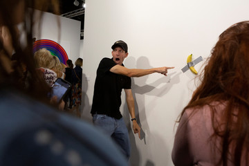 A man poses for a photo next to a banana attached with duct-tape that replaces the artwork 'Comedian' by the artist Maurizio Cattelan, which was eaten by David Datuna, in Miami Beach