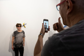 A woman poses for a photo next to a banana attached with duct-tape that replaces the artwork 'Comedian' by the artist Maurizio Cattelan, which was eaten by David Datuna, in Miami Beach