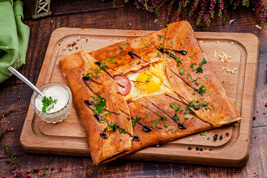 French cuisine concept. Creperie. Thin pancakes stuffed wrapped in an envelope. Dish on a wooden board. Beautiful serve in the restaurant.