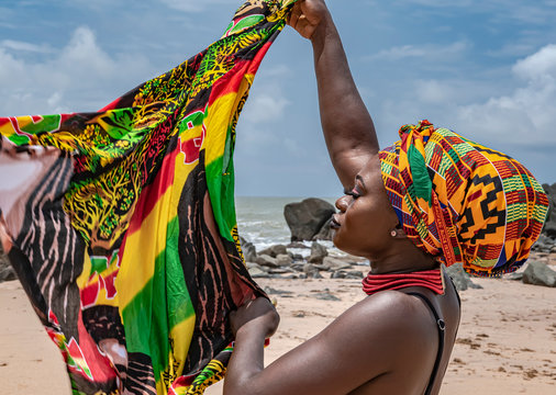 Ghana woman on the beautiful beach of Axim, located in Ghana West Africa. Headdress in traditional colors from Africa.