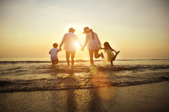Summer vacations. Happy family is holding hands running on the beach at sunset. Father and mother and little children are having fun on a tropical beach.