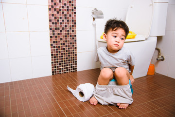 Asian little  kid 2-3 years old sitting on a kid bathroom accessory toilet