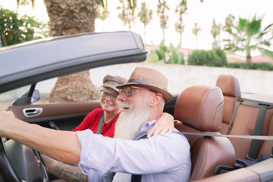 Couple inside a convertible car in a romantic moment  - Retired couple having fun doing a road trip during vacation - Travel, fashion and joyful elderly concept - Focus on man face