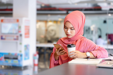 Beautiful young asian muslim business woman in pink hijab and casual wear working with laptop and business report at creative co-working.