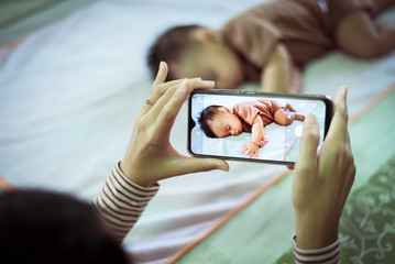 Mother hands taking a picture to baby boy with smart phone,Family memory concept,Close up