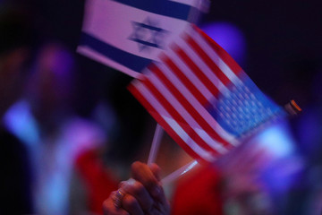 An audience member waves Israeli and American flags before a speech by U.S. President Trump at the Israeli American Council National Summit in Hollywood, Florida