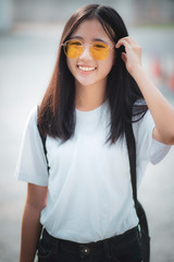 pretty asian teenager wearing eye glasses standing outdoor