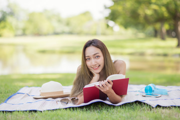 Cute girl read book in summer park