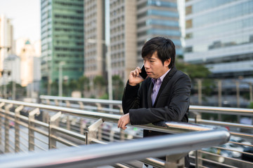 Korean Businessman talking over phone in city