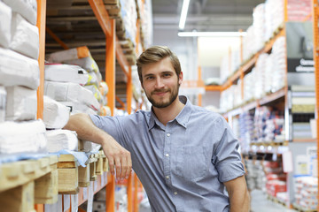 portrait of a smiling young warehouse worker working in a cash and carry wholesale store. Wall mural