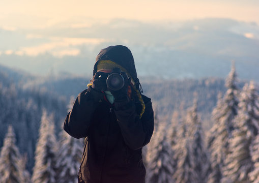 Girl is photographing in winter mountains