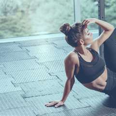 Portrait of fit muscular flexible sportswoman stretching legs, image with cold vintage toning