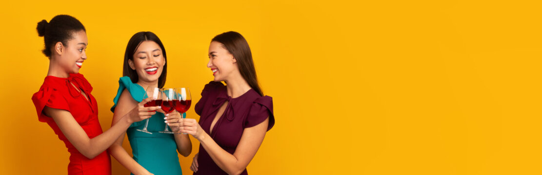 Three Women Clinking Red Wine Glasses Laughing Standing, Yellow Background
