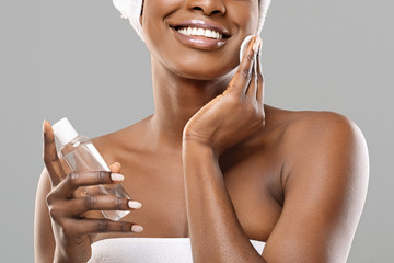 Fototapete - Unrecognizable afro girl cleaning face from makeup with micellar water