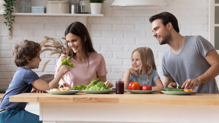Couple with children sitting at kitchen countertop preparing healthy dinner