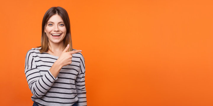 Portrait of attractive happy woman with brown hair in long sleeve striped shirt standing, pointing at copy space wall for promotional information. indoor studio shot isolated on orange background