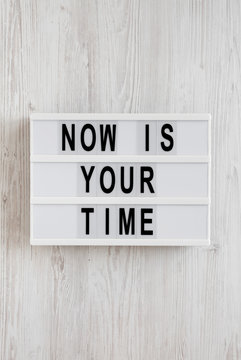 'Now is your time' words on a modern board on a white wooden background, top view. Overhead, from above, flat lay.