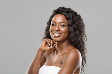 Fototapete - Young pretty african american woman with natural makeup on grey background