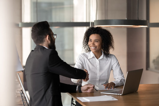Smiling diverse business partners handshake closing deal at meeting