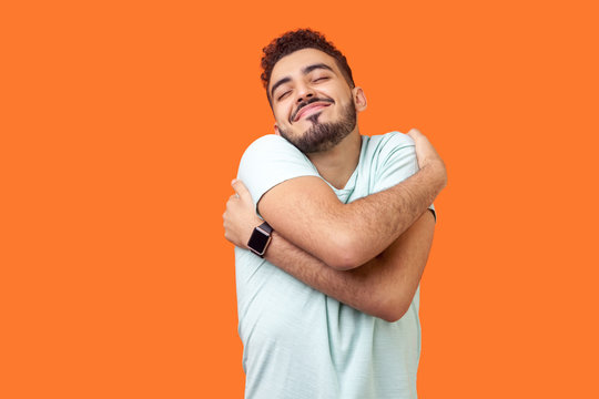 I love myself! Portrait of egoistic brunette man with beard in white t-shirt standing with closed eyes, embracing himself and smiling form pleasure and proud. indoor, isolated on orange background
