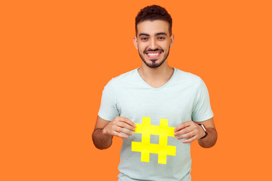 Promotion in social media. Portrait of happy brunette man with beard in white t-shirt smiling and holding big hashtag sign, sharing viral content. indoor studio shot isolated on orange background