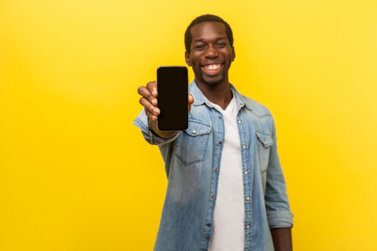 Online service, technology. Portrait of satisfied glad young man in denim casual shirt standing holding out cellphone and smiling broadly at camera. indoor studio shot isolated on yellow background