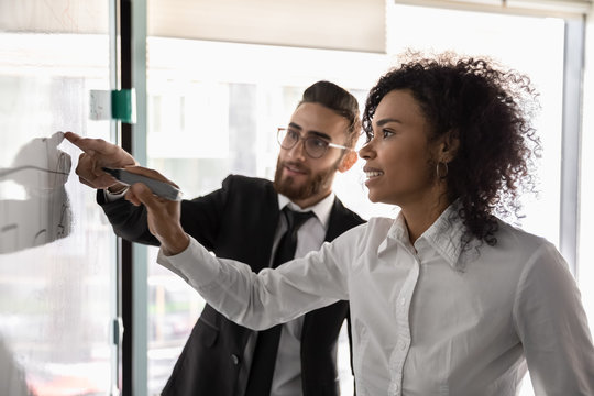 Multiethnic businesspeople develop business strategy on whiteboard