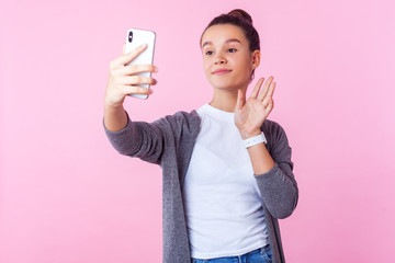 Portrait of beautiful positive teenage girl with bun hairstyle in casual clothes smiling and waving hello, hi gesture, communicating with friends on video chat. studio shot isolated, pink background