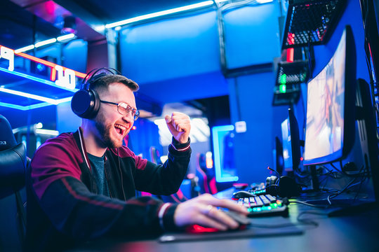 Professional gamer playing tournaments online video games computer with headphones, red and blue