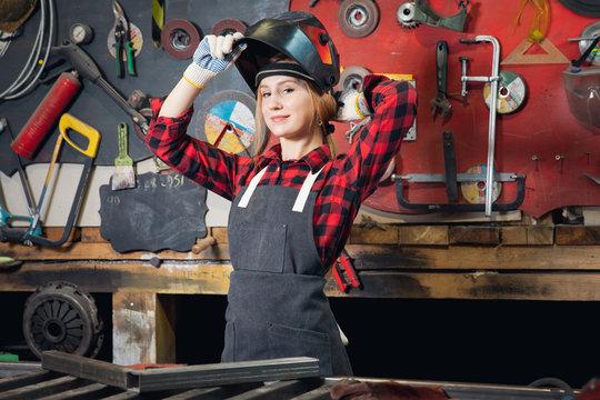 Beautiful girl engineer in mask welder is preparing for industrial work