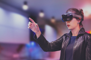 Portrait of young Caucasian woman using augmented and virtual reality with holographic hololens glasses. Pink, magenta, blue blurred background. Future technology concept.
