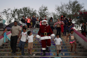 Santa Claus delivers gifts to asylum-seeking children who live in an encampment in Matamoros