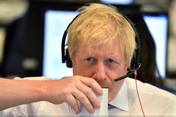 Britain's Prime Minister Boris Johnson takes a drink as he speaks to a caller on the phone at the Conservative Campaign Headquarters Call Centre in central London