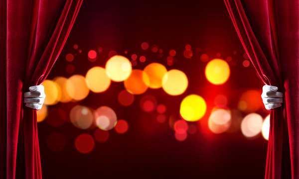 Bokeh lights behind drapery curtain and hand opening it