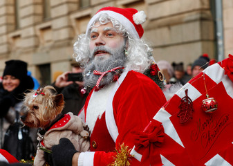 A man dressed as Santa Claus holds a dog as he takes part in the charity Santa Fun Run in Riga