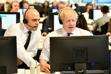 Britain's Chancellor of the Exchequer Sajid Javid and Britain's Prime Minister Boris Johnson speak to callers at the Conservative Campaign Headquarters Call Centre in central London