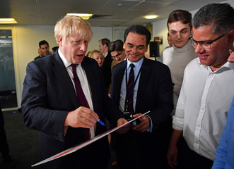 Britain's Prime Minister Boris Johnson signs placards for activists and supporters at the Conservative Campaign Headquarters Call Centre in central London
