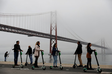 Tourists drive scooters next to 25th April bridge in Lisbon