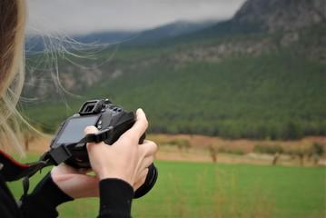 chica revisando una fotografía en el campo