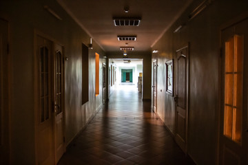 Dark corridor in the hospital. A long terrible corridor with light from the windows. Scary way.