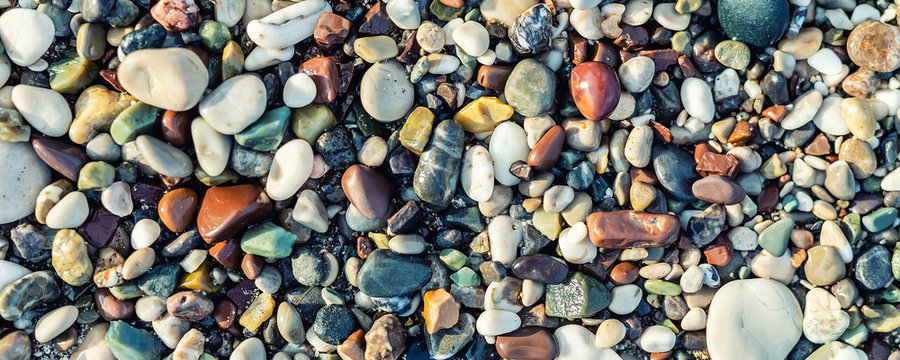Trendy colorful small sea stone pebble background. Multicolored abstract beach nature pattern