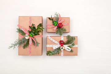 Christmas composition. Christmas gift boxes decorated fir tree branches and bells on white background. Christmas, winter, New Year concept. Flat lay, top view, copy space