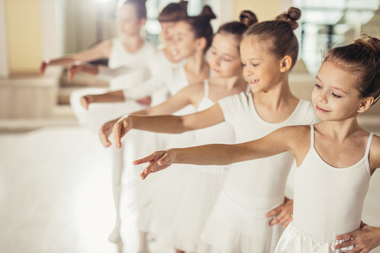 little kids ballerinas in studio, wearing white tutu skirts, stand in pose, performing classic ballet dance, smooth movements