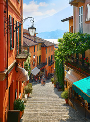 Spoed Fotobehang Milan Bellagio village at lake Como near Milan Italy, region Lombardy. Famous street with paving stones stairs and cosy restaurants during sunrise with glowing lanterns and green plants on old houses walls.