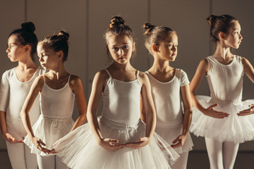 group of caucasian cute girls 7-8 years old dancing classic ballet together wearing white tutu skirts and pointe shoes