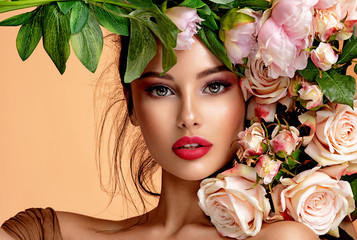 Spoed Fotobehang Bloemenwinkel Beautiful white girl with flowers. Stunning brunette girl with big bouquet flowers of roses. Closeup face of young beautiful woman with a healthy clean skin. Pretty woman with bright makeup