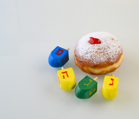 Fresh traditional  donut with jelly and wooden dreidels for Hanukkah celebration. Hebrew letters on color dreidels say : Great Miracle Happened Hear.