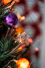 Christmas background. Detail view of red and silver baubles and festive decorations hanging on a green christmas tree.