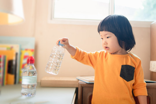 Cute 2 year old Asian toddler girl concentrates lifting and trying to hold a water bottle with her one hand, using fine motor skills, children's development, sensory activity with natural sunlight.